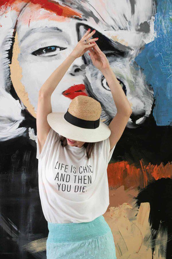 """תמונת אווירה - קריאייטיב ליין - דוגמנית עומדת על רקע ציור גדול עם חולצה לבנה עליה כתוב (באנגלית) : """" החיים הם שיק ואז אתה מת"""""""