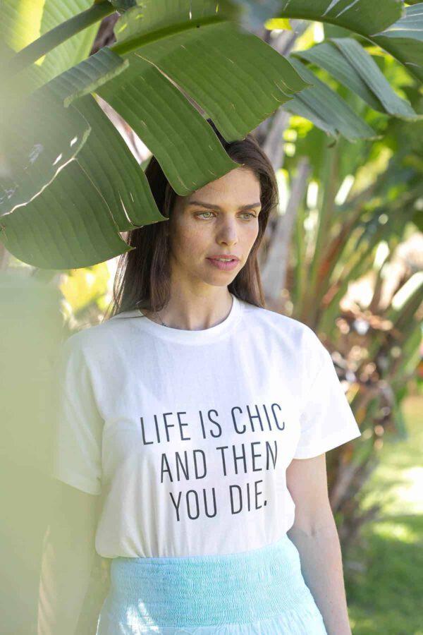 """תמונת אווירה - קריאייטיב ליין - דוגמנית עומדת על רקע עץ ירוק עם חולצה לבנה עליה כתוב (באנגלית) : """" החיים הם שיק ואז אתה מת"""""""