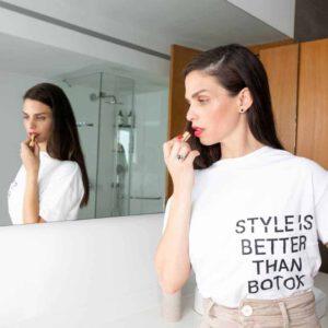"""מוצר למכירה על גבי דוגמנית: חולצה לבנה עם כיתוב באנגלית """"סטייל זה יותר טוב מבוטוקס"""""""